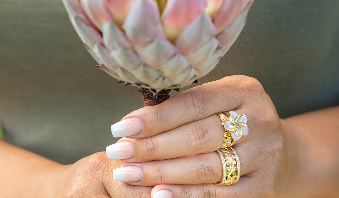 Model Wearing Protea Ring and Hawaiian Heirloom Ring and Holding Protea Flower
