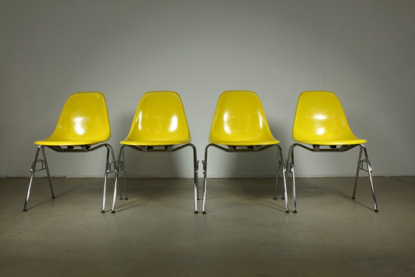 Eames Fibreglass dining chair in yellow with stacking legs