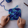 Woman's hands with a blue crochet granny square, a matching yarn ball, and a wooden crochet hook all on a gray background