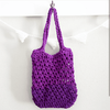 Purple crochet tote bag hanging on a white wall