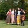 5 women wearing sari wrap skirts with their arms around eachother standing in the grass