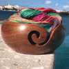 Yarn bowl holding a ball of multicolored yarn while sitting on a stone surface in front of a body of water