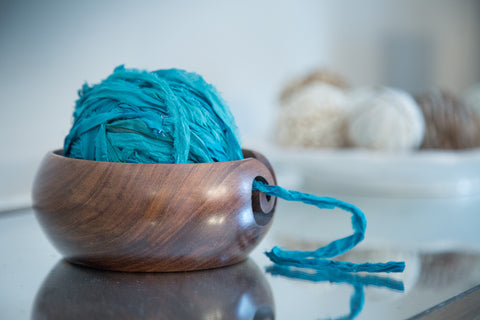 Handmade wooden yarn bowl holding a blue ball of yarn on a glass surface