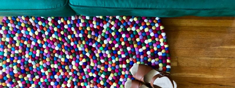 Felt Ball Rug Laying on floor with a green couch