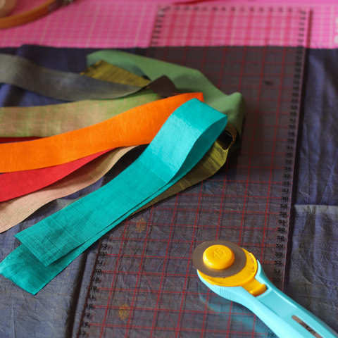 Multicolored strips of silk fabric sitting on top of a rotary mat with a rotary cutter and large ruler
