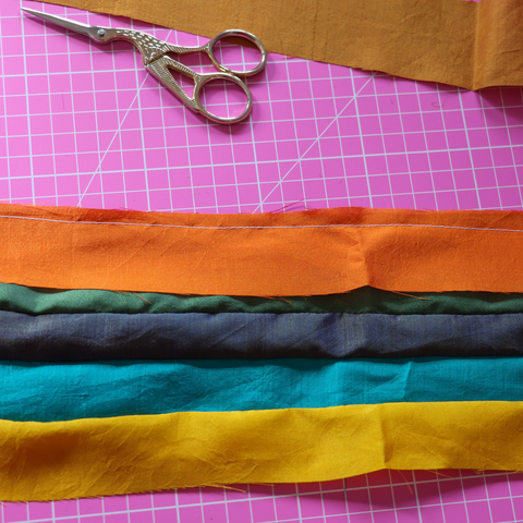 Several strips of silk sewn together sitting on a rotary cutting mat with a pair of embroidery scissors