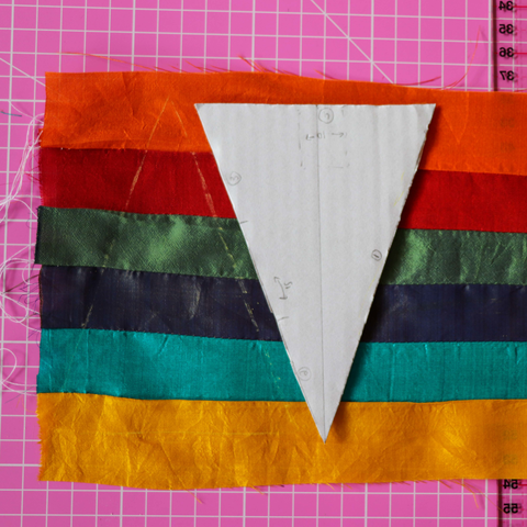 Triangular piece of paper set on several strips of silk sewn together on a rotary cotton mat