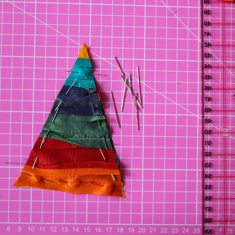 Two triangular pieces of silk fabric pinned together on a pink rotary cutting mat