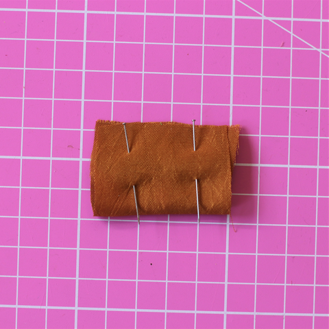 Small brown piece of silk sitting on a pink rotary cutting mat