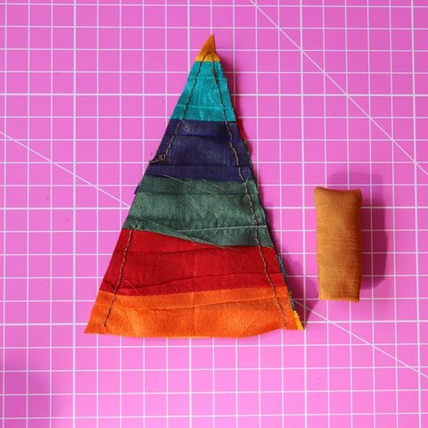 Silk Triangle and small brown stuffed silk tube sitting on a pink rotary cutting mat
