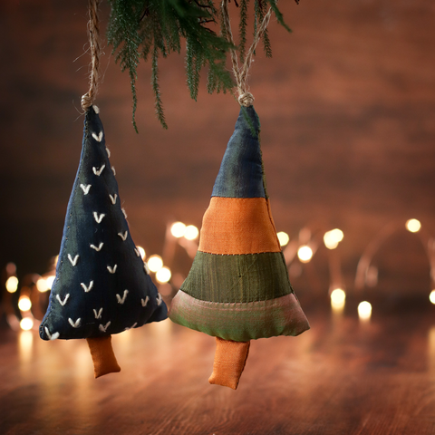Two handmade silk Christmas tree ornaments hanging from a lit Christmas tree