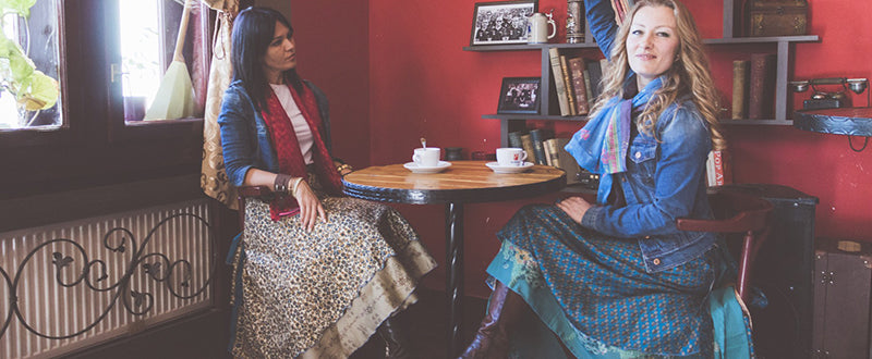 Two women wearing darn good yarn sari wrap skirts at a cafe drinking coffee together smiling