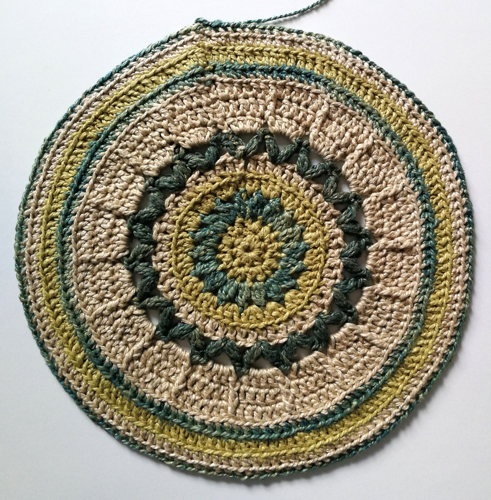 Tan and green patterned crochet circle on a white background