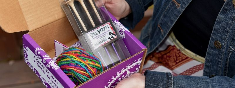 Women holding the first month box of Yarn of the Month. It's a purple box with watercolor yarn inside and ombre knitting needles and crochet hook.
