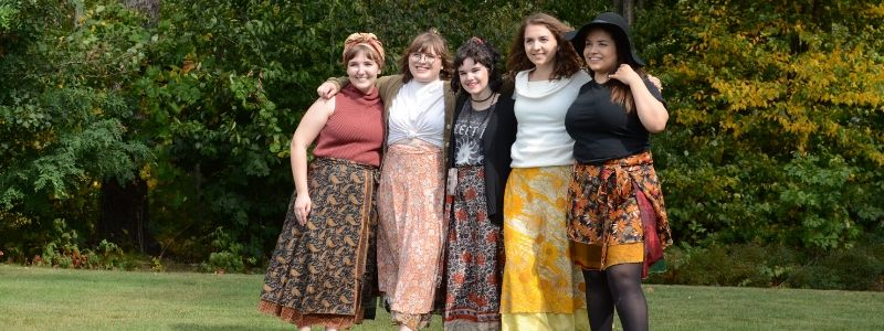 Five Women wearing sari wrap skirts looking happy!