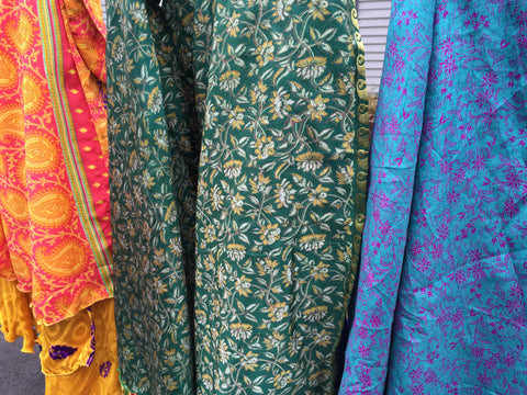 Three sari skirts (orange, green, and blue) are hanging in front of a window.