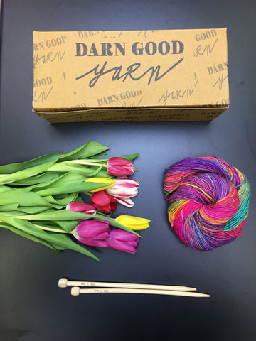 A bouquet of tulips, wooden knitting needles, a multicolored ball of yarn, and a Darn Good Yarn of the Month brown box on a black background