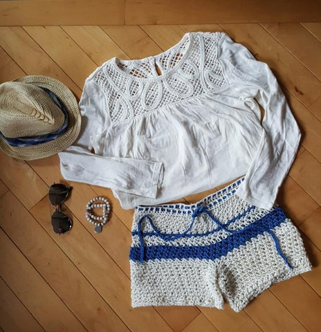 Crocheted Oasis Shorts, long sleeved white tee shirt, hat and sunglasses all on a wooden surface