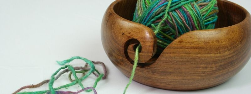 Handmade wooden yarn bowl with worsted weight green yarn inside
