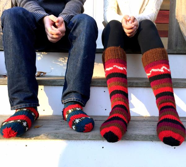 Man and woman sitting next to each other on a wooden staircase and both wearing multicolored striped wool knit socks