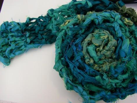 Teal knitted scarf rolled up onto a white surface
