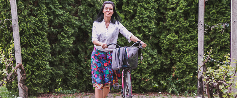 Women wearing sari wrap skirt standing next to her bike in front of tall hedges in bloom