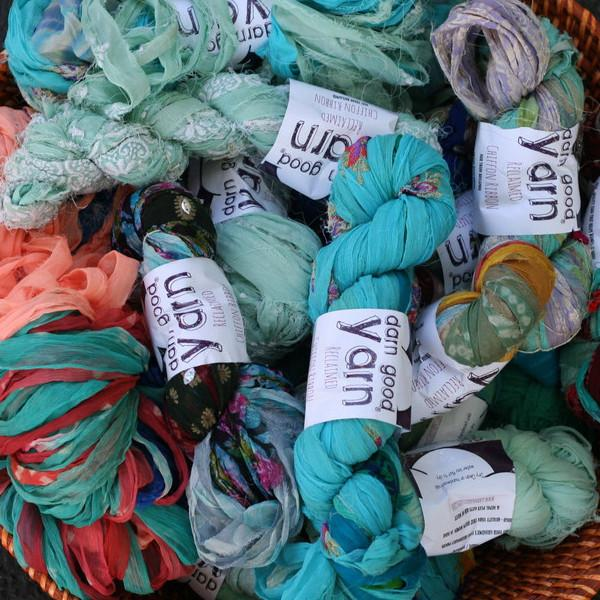 Multiple skeins of multicolored sari silk ribbon yarn all with white Darn Good Yarn labels