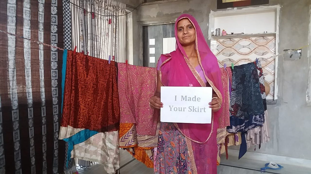 "Artisan in India holding a sign that says ""I made your skirt"" in front of sari wrap skirts"