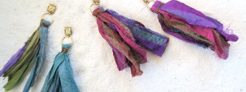 A blue pair and a purple pair of Moroccan Dreams Earrings laying in white sand