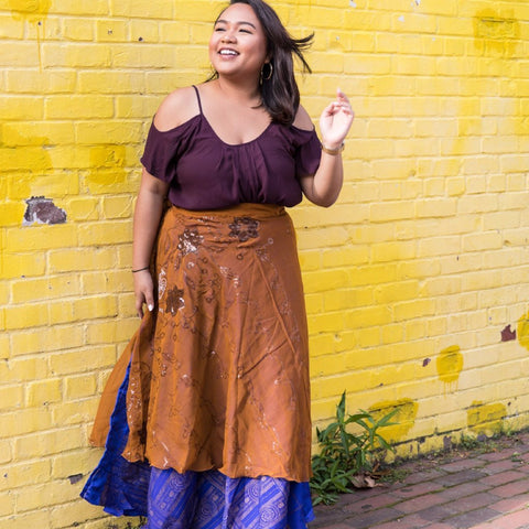Woman wearing a sari wrap skirt and purple top standing in front of a yellow brick wall