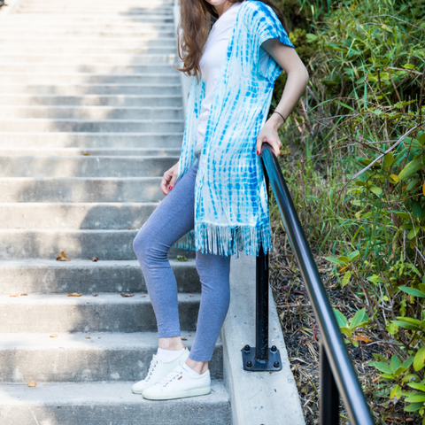 Woman wearing a yarn fringe kimono cover up with leggings and a tee shirt and standing on a concrete staircase leaning against metal railing
