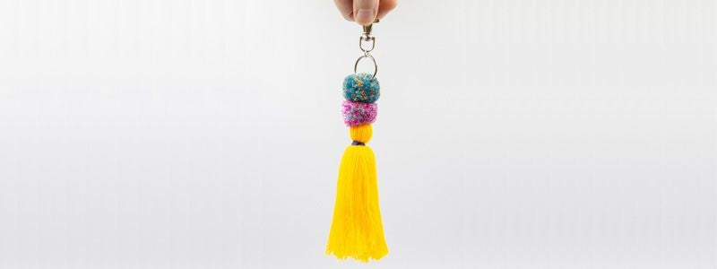Pom Pom Tassel being held by the clip on a grey background