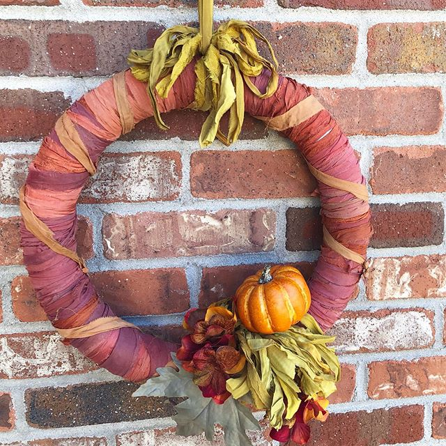 ribbon-wrapped orange fall wreath decorated with fall leaves, pumpkins, and flowers, hung on a brick wall