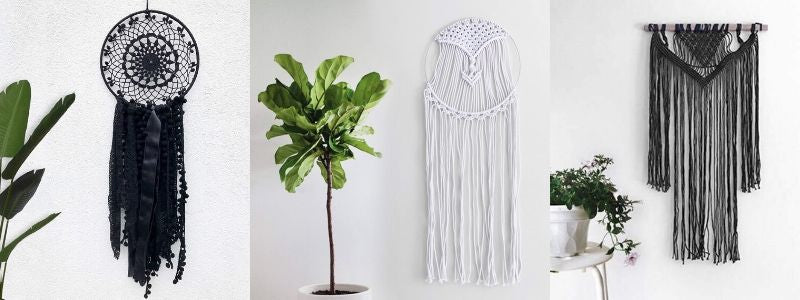 Three macrame tapestries hanging. Two are black one is white