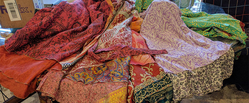 Five darn good yarn sari wrap skirts laying on a table right after being opened from the shipping box
