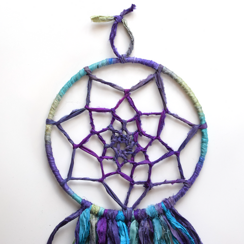 Using small piece of sari ribbon and tying it to the opposite end of the loop to hang the dream catcher.