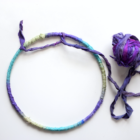 Starting the inside web of the dreamcatcher with purple recycled sari silk ribbon yarn