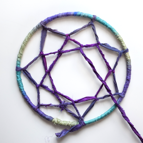 Looping around the center lines of ribbon with the same beautiful purple colored recycled sari ribbon yarn