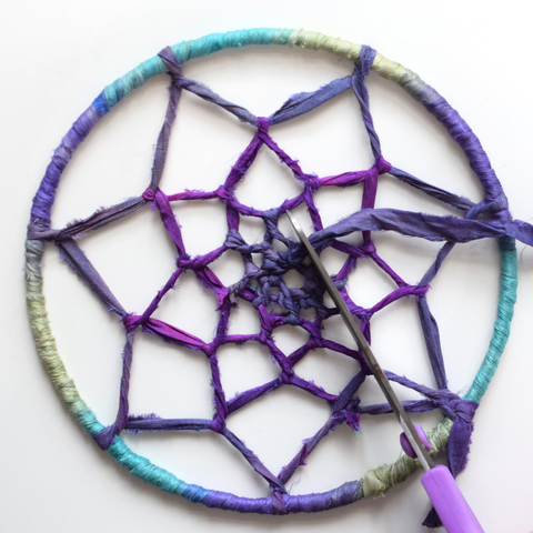 Finished picture of inner webbing of dreamcatcher cutting off the excess ribbon.
