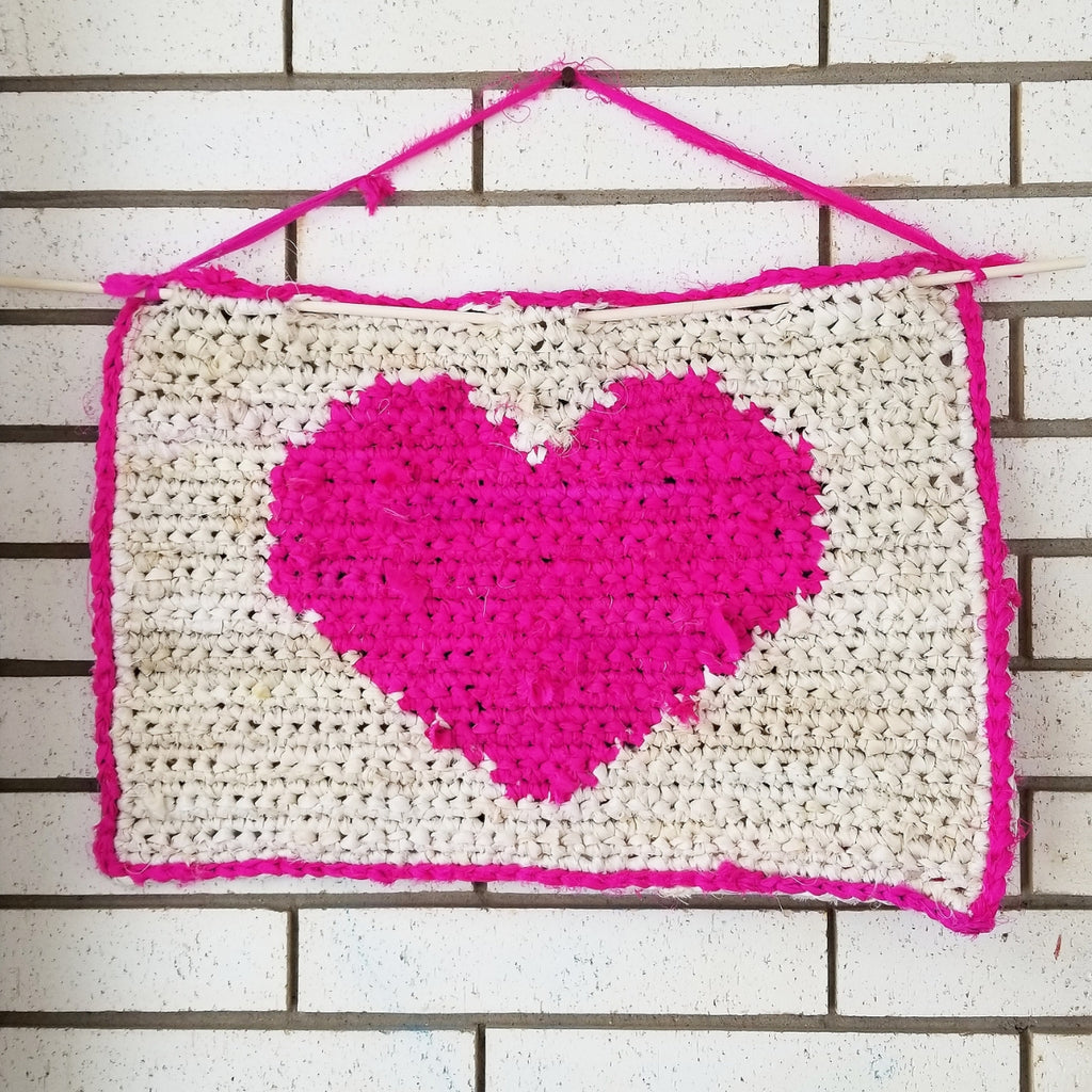 Pink and white all my love wall hanging hung from a white brick wall