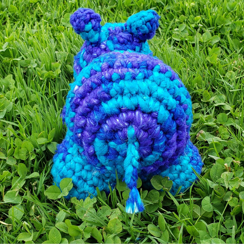 Blue crochet baby hippo sitting on grass