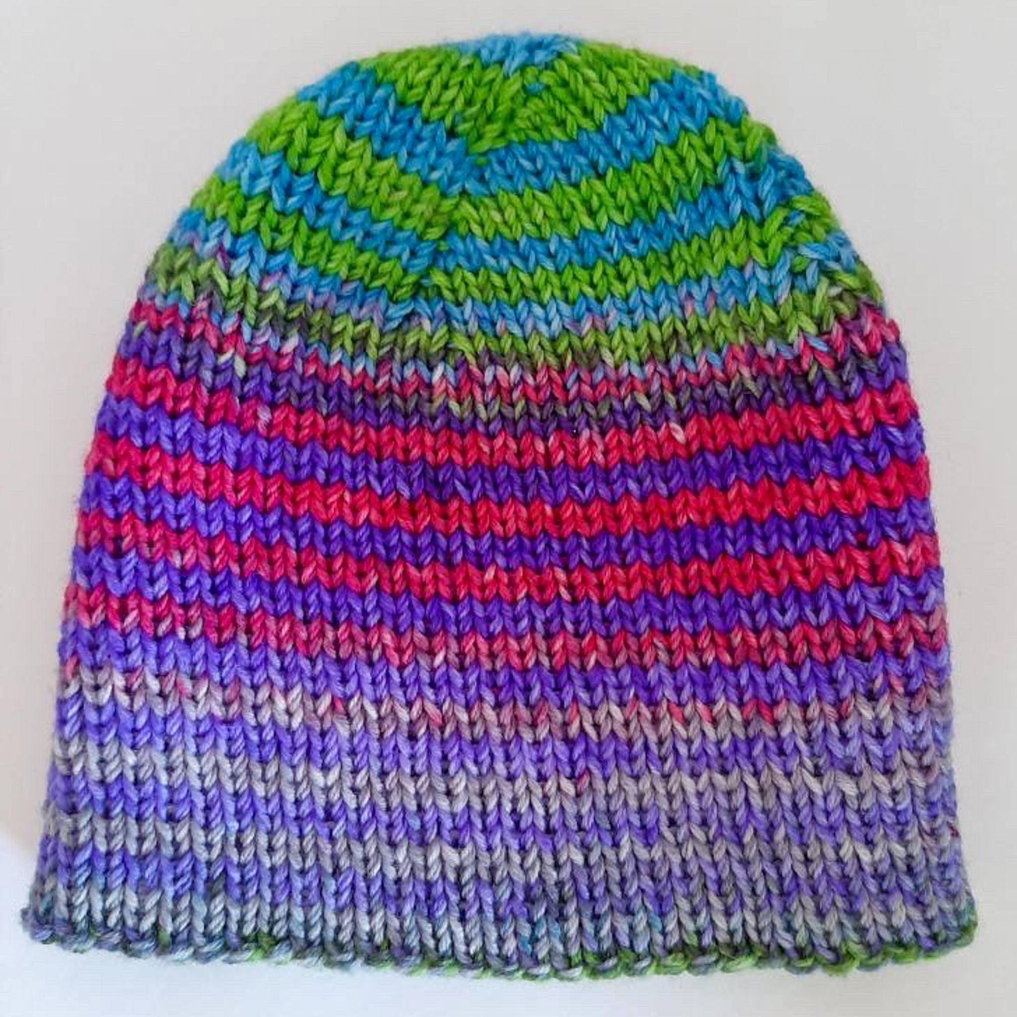 Flattened view of finished Boss Beanie showing the progression of colors from green and blue at the top to pink and purple to gray and purple at the bottom.