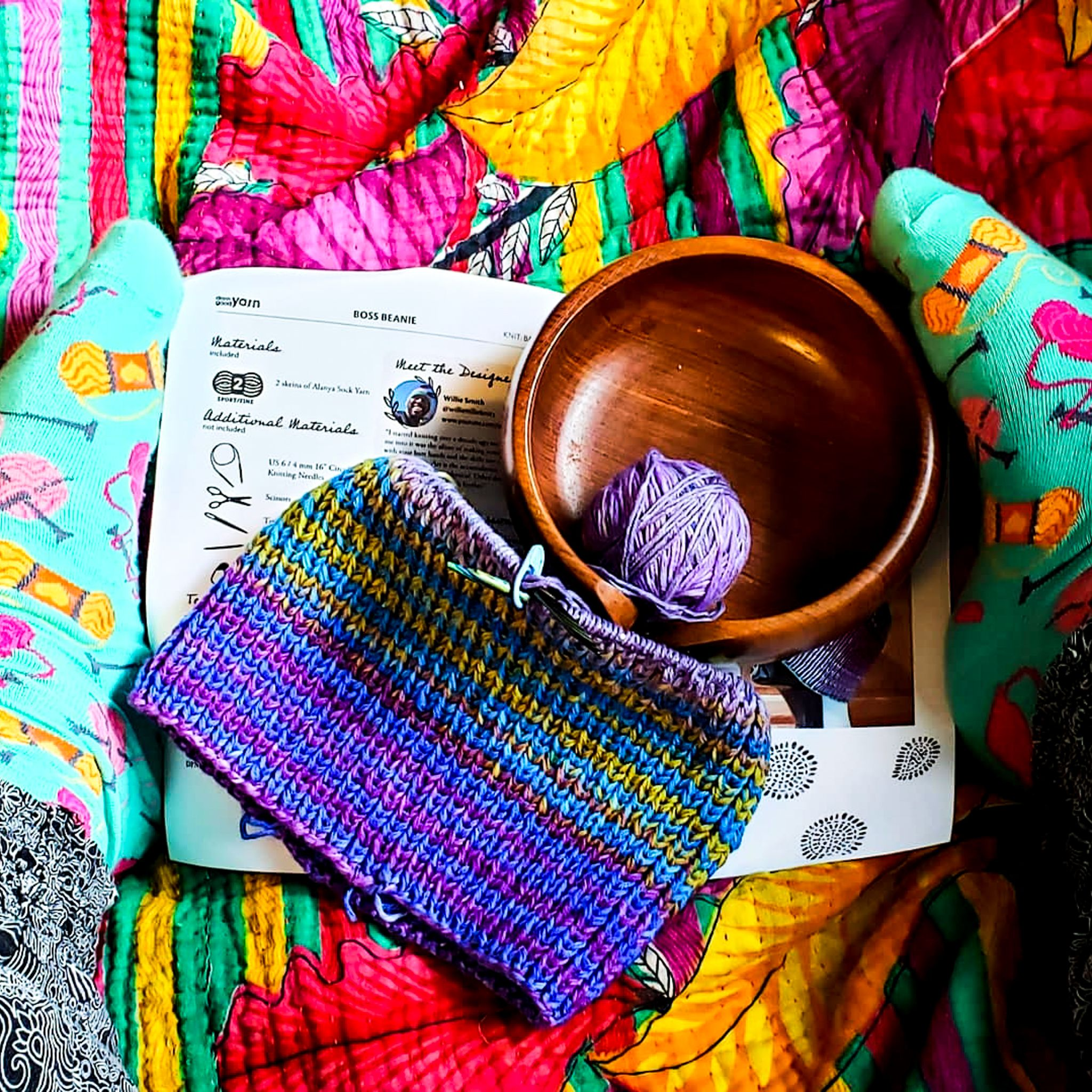 Photograph of boss beanie work in progress showing purple, blue, teal and yellow striped sections complete on top of colorful blanket with yarn bowl.