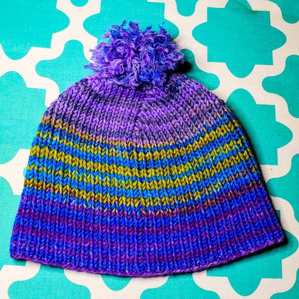 Photograph of finished boss beanie. Blue and purple, teal and yellow, and purple striped sections complete on top of teal patterned background.