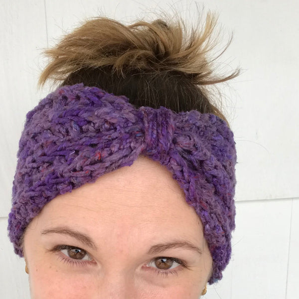 Bow Ear Warmer in purple worn on a woman's head in front of a white background