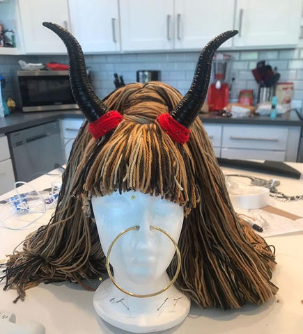 Another of Collin's wigs being displayed on a white mannequin head. This wig is made with brown yarns, and has horns like a bull!