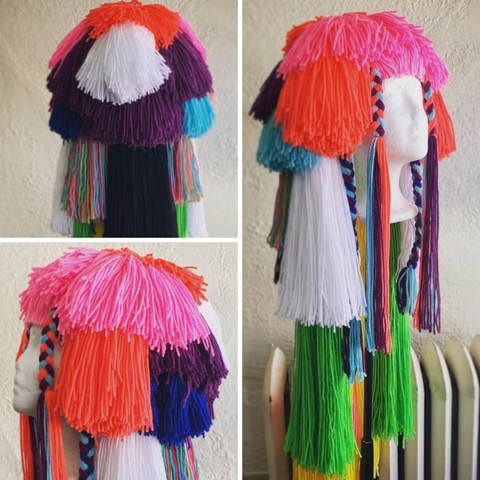 Collin's multicolored wig being shown on a white mannequin head, at 3 different angles.