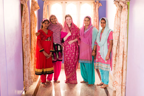 This is a picture of our founder and CEO, Nicole, along with some of our artisans. They are each wearing different colored saris in a brightly lit room.
