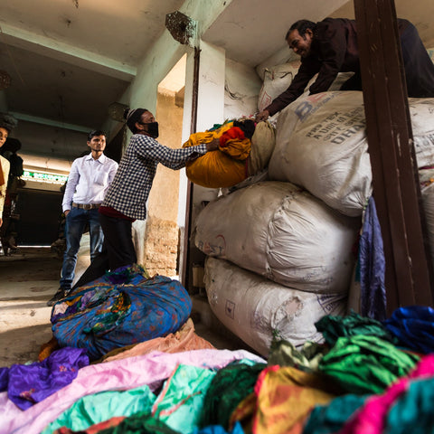 A man is crouching on top of large bags of recycled fabric. He is passing down the bags to two men who are waiting to take the fabric to be made into skirts. Sari fabric litters the floor, ready to be made into skirts or yarn.