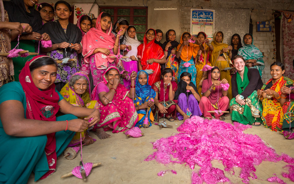 Multiple women wearing colorful saris crouching for a group photo over a dirt floor covered in hot pink yarn fibers